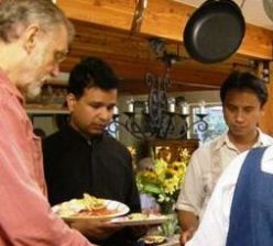 Fr. Ranjan D'Sa, with Bob Lewis on his left, at the potluck lunch.
